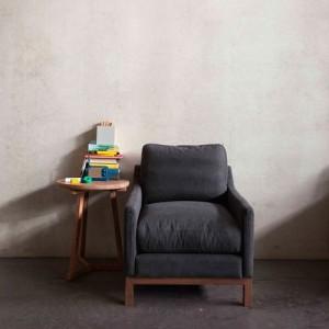 Mesa auxiliar Tripod en roble junto a un cómodo sillón negro