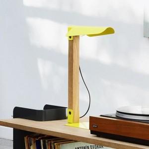 Lámpara de sobremesa Merlin en color amarillo apoyada en escritorio de Ethnicraft.